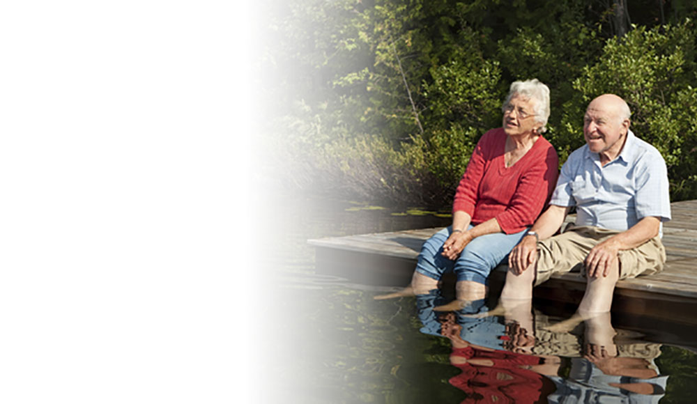 Elderly couple dipping feet in lake